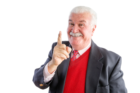 homily: Close up of cheeky senior wearing a business suit with red sweater smiles at the camera and points up Stock Photo