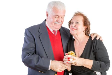 hugged: Proud senior woman holding her Valentines gift as she smiles at the camera while being, hugged by her loving husband, upper body isolated on white Stock Photo