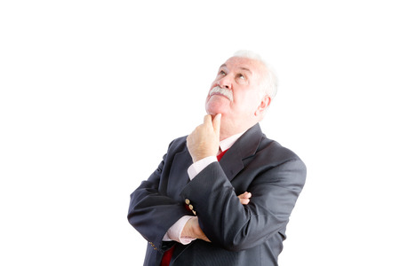 speculative: Thoughtful white haired senior businessman standing with his hand to his chin staring up into the air with a serious expression, upper body isolated on white Stock Photo