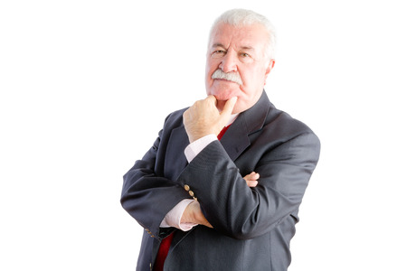 introspective: Half body portrait of thoughtful mature businessman in suit with hand on chin, white background Stock Photo