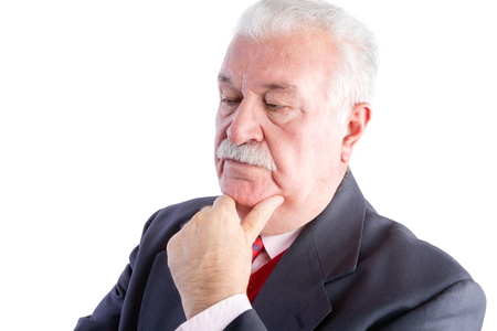 inscrutable: Portrait of serious thoughtful mature businessman with hand on chin, white background
