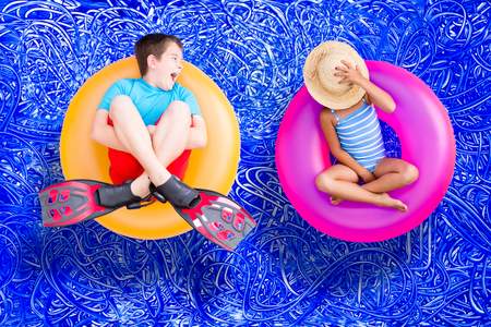 Raucous little boy and his quiet young sister relaxing together on bright colorful plastic rings in the swimming pool enjoying a hot summer day, conceptual image on blue painted water background with ripples photo