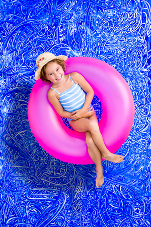 Happy little 5 year old girl enjoying her summer vacation floating in the swimming pool on a bright pink tube and grinning at the camera, conceptual image on blue painted water background with ripples photo