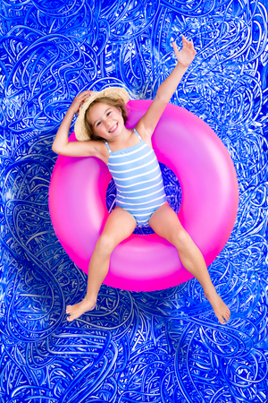 Confident happy little 5 year old girl in a swimming pool floating on a bright pink plastic tube in her swimsuit waving at the camera with a cheerful grin, conceptual image on blue painted water background with ripples photo