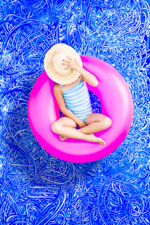 sunhat: Young 5 year old girl spending a relaxing day in the pool floating on a colorful pink plastic tube with her sunhat over her face, conceptual image on blue painted water background with ripples