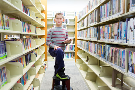 Happy boy in library surrounded by book shelves with foot on stool