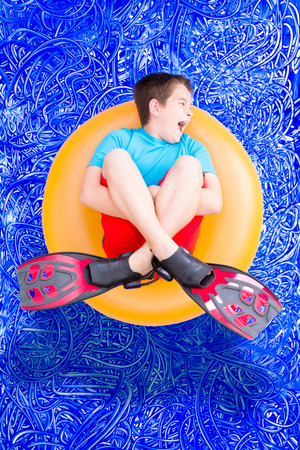 Loud noisy little boy playing in a swimming pool on a hot summer day floating in a plastic ring in his flippers, conceptual image on blue painted water background with ripples
