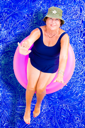 elderly woman: Elderly lady in a stylish hat and swimsuit floating on a tube in the swimming pool relaxing on a hot summer day looking up to wave at the camera, conceptual image on blue painted water background with ripples Stock Photo