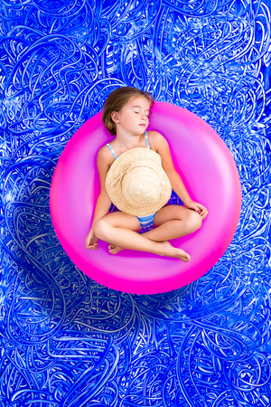Cute young girl 5 year old taking a nap in the swimming pool as she relaxes on a colorful pink plastic tube in her swimsuit and sunhat, conceptual image on blue painted water background with ripples photo
