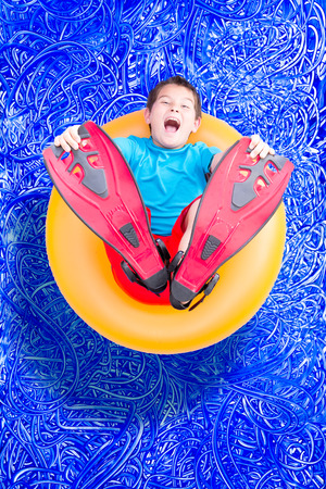 Young boy in flippers playing in a summer swimming pool lying back on a floating yellow ring laughing at the camera, conceptual image on blue painted water background with ripples