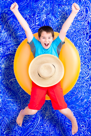 Cheerful little boy celebrating his summer holiday floating in a colorful yellow tube in the pool laughing and extending his arms, conceptual image on blue painted water background with ripples photo