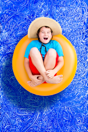 Happy young boy relaxing in a summer swimming pool in his colorful shorts, top and sunhat laughing up at the camera as he floats of a plastic tube, conceptual image on blue painted water background with ripples photo