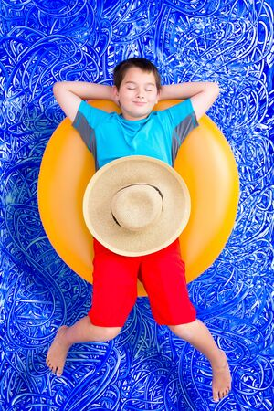 Handsome little boy dozing off in the swimming pool relaxing on a bright yellow tube with closed eyes and a blissful smile, conceptual image on blue painted water background with ripples photo