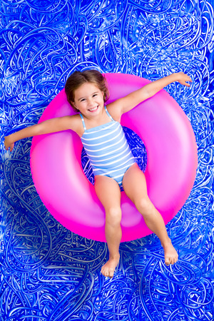 Happy young girl floating in a summer pool on a colorful pink plastic ring looking up at the camera with a lovely friendly smile, conceptual image on blue painted water background with ripples photo