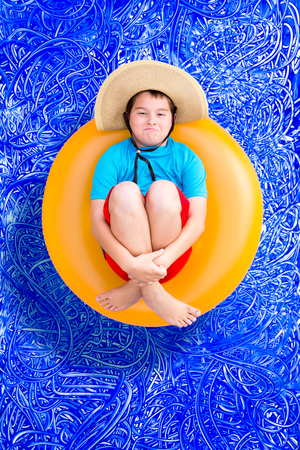 buoyancy: Playful young boy in a summer swimming pool relaxing on a floating yellow ring grinning up at the camera in a big straw hat, conceptual image on blue painted water background with ripples