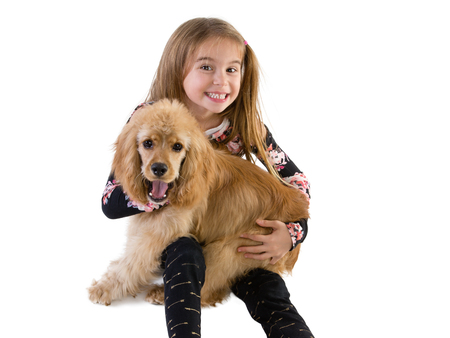 Young girl grinning at the camera as she hugs her puppy, a cute little golden cocker spaniel, in her arms over white