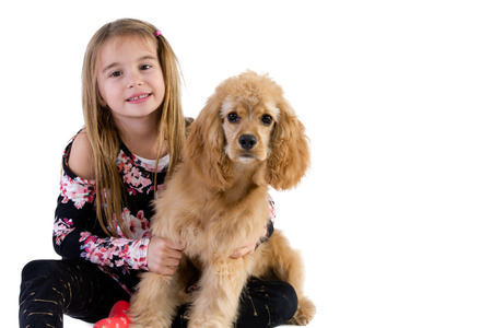 Pretty young girl hugging her golden cocker spaniel puppy as she relaxes on the floor with the dog isolated on white