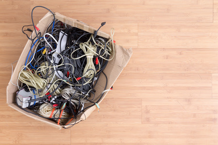 Old battered cardboard box with electrical cords and connectors for electronic devices on a wooden background with copy space viewed from above 版權商用圖片
