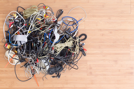 Messy tangle of old electric cords and connectors awaiting discard on a wooden surface with copy space in an overhead view