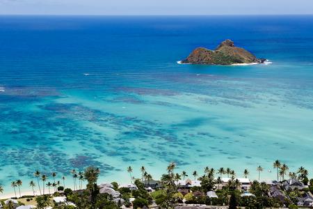 Horizontal view of Hawaiis Mokulua Islands on turquoise Pacific Ocean, over the Lanikai town from Kalwa Ridge sitting on Pillbox Hike.