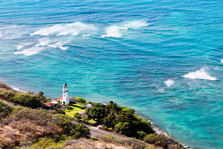 The Diamond Head lighthouse, Oahu, Hawaii southeast of Honolulu in a scenic aerial view with azure ocean and rocky reefs Stock Photo