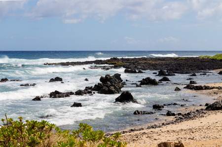 Crashing waves on black volcanic rocks, Oahu, Hawaii along the rocky shoreline at the edge of a sandy beach Stock Photo