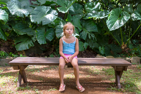 Bored little girl sitting on a bench in paradise amongst lush green tropical vegetation on a Hawaiian vacation Foto de archivo - 94352401
