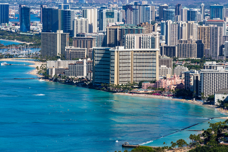 Old beachfront hotels in Waikiki lining the coastline in the popular tourist attraction and resort in Honolulu, Oahu, Hawaii with a calm blue Pacific Ocean