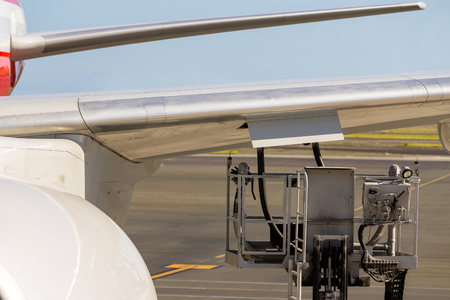 Wing of an aircraft during fuelling with an elevated motorised platform with rubber pipes parked under an open flap on the apron at an airport in a concept of aviation and travel Stock Photo