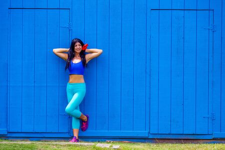 Alluring young woman with a hibiscus in her hair posing leaning against a bright colorful blue wooden wall in Oahu, Hawaii with a happy smile
