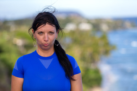 Young woman pulling faces pouting at the camera as she poses overlooking the coastline on Diamond head, Oahu, Hawaii