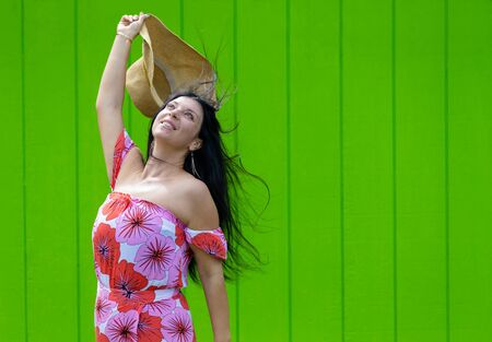 Carefree happy woman rejoicing in Hawaii raising her straw sunhat on high with her long hair blowing in the breeze in front of a vivid green timber wall with copy space