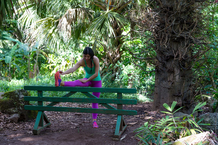 Athletic young woman working out in a lush green park in Oahu, Hawaii doing stretching exercise using a rustic wooden bench for support Stock Photo