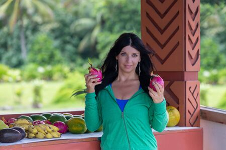 Pretty young woman holding up two fresh Dragon fruit on an open air covered patio in Hawaii as she smiles at the camera with greenery backdrop Stock Photo