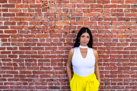 Serious fashionable young woman in yellow pants standing with her hands in her pockets in front of a brick wall with copy space