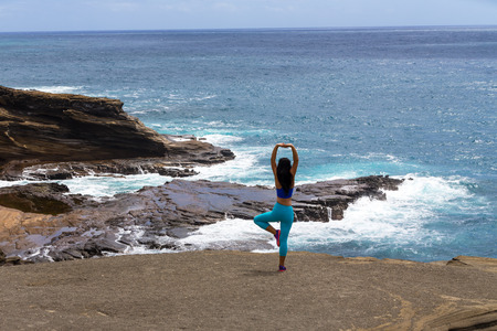Sporty slender woman working out at heavens Point doing yoga exercises standing on a rocky ledge overlooking the Pacific Ocean in Hawaii