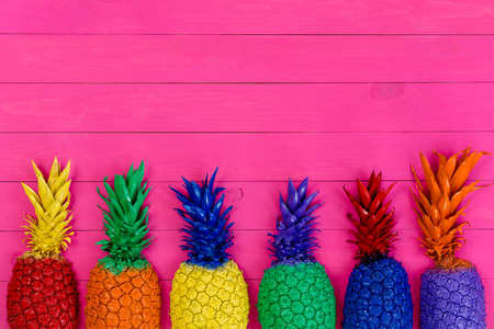 Row of colorful painted pineapples with their leaves in the colors of the rainbow or spectrum on a vivid pink wooden background with copy space