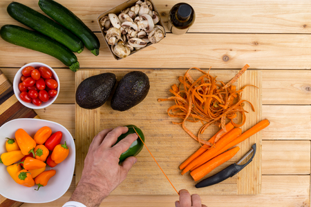 Chef slicing fresh vegetables for cooking on a wooden chopping board holding a green pepper with peeled carrots, zucchini, mushrooms, tomatoes,ripe avocado pears and carrots in an overhead view Stock Photo