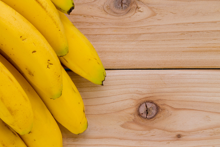 Side border of a bunch of ripe yellow tropical bananas over a wooden background with knots and copy space