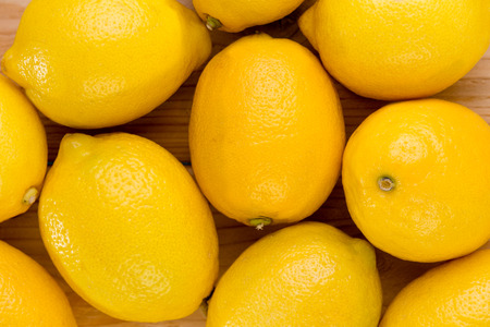 Close-up high-angle full frame view of fresh and juicy yellow lemons on a wooden table