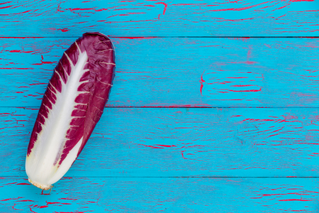 Single head of fresh leafy radicchio or Italian chicory forming a side border over a blue crackle painted wooden background with copy space Stock Photo