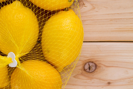 Plastic net bag filled with ripe yellow lemons on a wooden background with copy space in a close up overhead view Stock Photo
