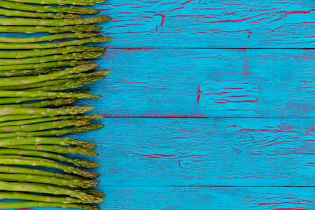 Border of healthy green asparagus shoots in spring on a turquoise blue wooden background with textured crackle paint and copy space