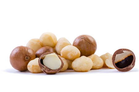 Pile of fresh macadamia nuts rich in nutrients with some whole shelled nuts, some nuts still in their shells and a few halved with loose shells on a white background Stock Photo