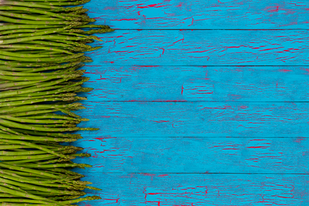 Side border of fresh green asparagus spears, tips or shoots on colorful blue crackle paint wood with copy space Reklamní fotografie