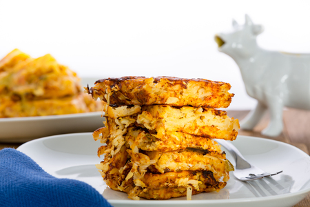 Stack of crispy waffle hash browns, or shredded potato pancakes, on a plate ready for a tasty breakfast in a low angle side view Stock Photo