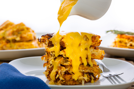 Pouring a rich cheese sauce from a white jug over a stack of golden crispy hash browns on a plate in a close up side view