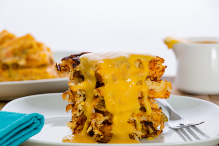 Delicious stack of crispy potato waffle or hash browns drizzled with melted cheese for a wholesome breakfast in a close up side view Stock Photo