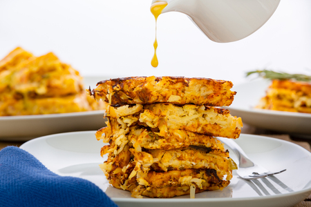 Side view of a stack of pan-fried hash browns with a jug above and suspended drip of a dressing or sauce being poured onto the top pancake Stock Photo