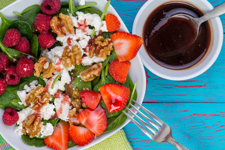 Tasty fresh salad with baby spinach and walnuts with fruit trimmings of ripe raspberry and strawberry on feta cheese served with a vinaigrette sauce Banque d'images - 94656068